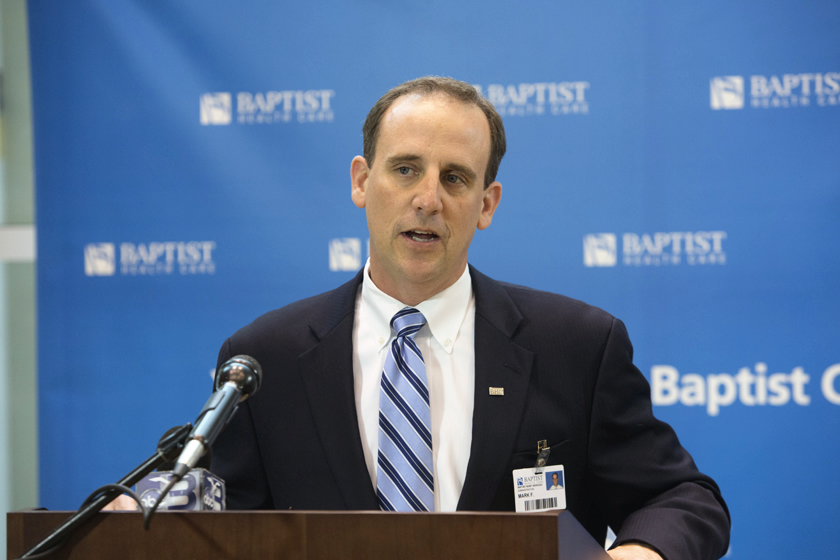 Mark Faulkner CEO of Baptist Health Care at podium announcing Baptist and Mayo teaming together.