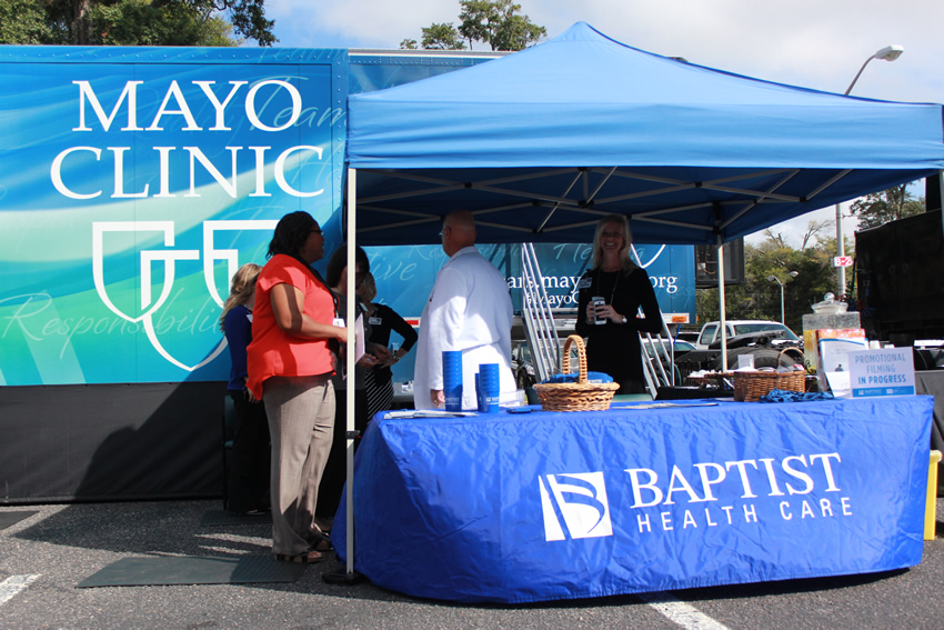 Visitors at Mayo Clinic Tent booth at Baptist Health Care Medical Towers.